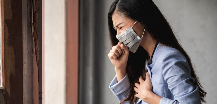 Woman in a mask with COVID symptoms